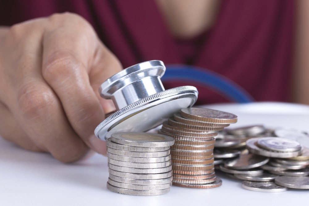 Financial concept, hand hold stethoscope and coins